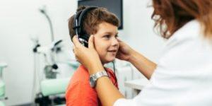 Audioloog plaatst koptelefoon bij jongen